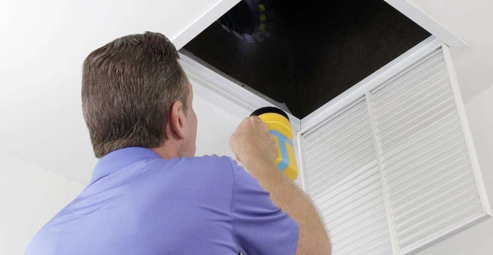 Man inspecting open HVAC vent with flashlight